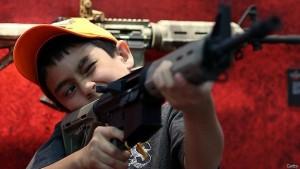 Un niño sostiene un arma durante la convención anual de la Asociación Nacional del Rifle de EE.UU. (NRA).