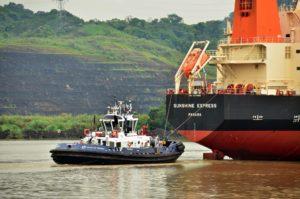 Un remolcador guía a un buque en tránsito en aguas del Canal de Panamá. (Foto: ACP).